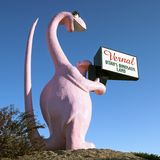 Pink dinosaur holding sign Stock Image