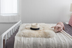 Pink doll on white wooden bed and classic hat Royalty Free Stock Photo