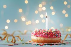 Free Pink Donut And One Burning Candle Against Bokeh Light Background. Happy Birthday Concept Stock Photography - 157414932