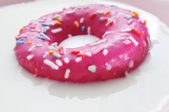 Pink donut being soaked in milk Stock Image