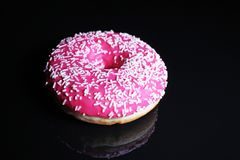 Pink donut on black reflective studio background Stock Images