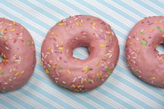 Pink donut on blue striped background Royalty Free Stock Image