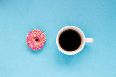 Pink donut with cup of coffee on the blue background. Delicious donut Stock Photography
