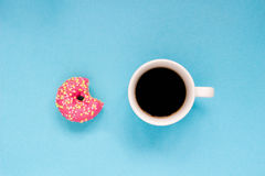 Pink donut with cup of coffee on the blue background. Delicious donut Royalty Free Stock Photo