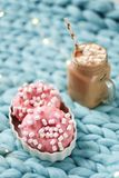 Pink donut with marshmallow and hot chocolate in glass cup on blue merino knit blanket. Lights on background. Pink donut with marshmallow and hot chocolate in Royalty Free Stock Photography
