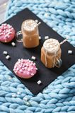 Pink donut with marshmallow and hot chocolate in glass cup on black tray on blue merino knit blanket. Lights on background. Pink donut with marshmallow and hot Stock Images