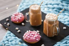 Pink donut with marshmallow and hot chocolate in glass cup on black tray on blue merino knit blanket. Lights on background. Pink donut with marshmallow and hot Royalty Free Stock Photos