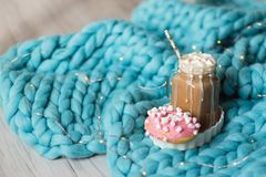 Pink donut with marshmallow and hot chocolate in glass cup on blue merino knit blanket. Lights on background. Pink donut with marshmallow and hot chocolate in Royalty Free Stock Photos
