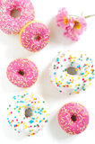 Pink donut. Sweet pink donut with sugar sprinkles and flowers royalty free stock photo