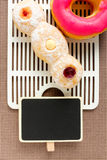 Pink donut and trio on tablecloth with blackboard Stock Image