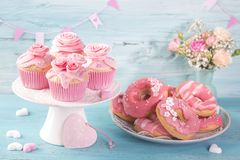 Pink donuts and cup cakes. On a blue background royalty free stock photography