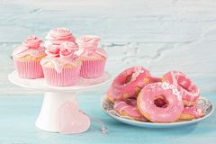 Pink donuts and cup cakes. On a blue background stock photography