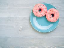 Pink donuts on gray wooden background, copy space, top view. Top view of two pink donuts on gray wooden background with copy space. Colorful donuts on plate with royalty free stock photo