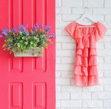 Pink door with flowers and a dress Stock Photo