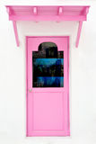 Pink door with sunshade. On white house Stock Images
