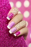 On pink dot. French manicure with pink shades and white dots on a brilliant background stock photography
