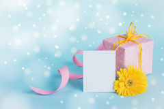 Pink dotted gift box, yellow gerbera flower and empty card over a blue background. Stock Photos