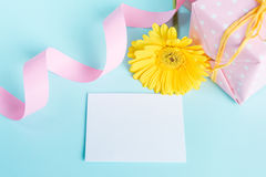 Pink dotted gift box, yellow gerbera flower and empty card over a blue background. Royalty Free Stock Image