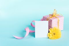 Pink dotted gift box, yellow gerbera flower and empty card over a blue background. Stock Image