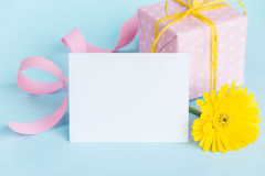 Pink dotted gift box, yellow gerbera flower and empty card over a blue background. Stock Images