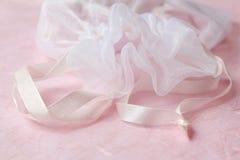 Pink drawstring bag with pink satin ribbon. Close up of white drawstring bag neck with pink satin ribbon on pink background Stock Image