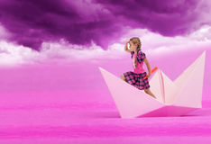 Pink dreams. Little girl sailing on paper boat under purple sky royalty free stock photos
