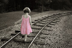 Pink dress. Colorized black and white with little girl in a pink dress walking on railroad track royalty free stock images