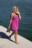 Pink dress dock hold shoes. A woman walking on the dock holding her shoes with a small smile on her lips Royalty Free Stock Photos