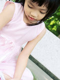 Pink dress girl on bench Royalty Free Stock Image