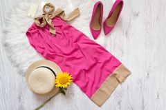 Pink dress with tag, shoes, hat and sunflower. Fashionable conceptPink dress with tag, shoes, hat and sunflower. Royalty Free Stock Images