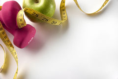 Pink dumbbells with apple and tape measure diagonal top Stock Photo