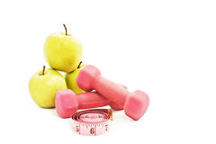 Pink dumbbells, green apple and measuring tape Royalty Free Stock Images