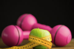 Pink dumbbells with green apple and measuring tape Stock Photography