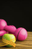 Pink dumbbells with green apple and measuring tape Royalty Free Stock Photo