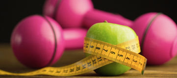 Pink dumbbells with green apple and measuring tape Royalty Free Stock Photography