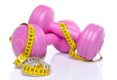 Pink dumbells with a tape measure. Isolated on white Royalty Free Stock Photos