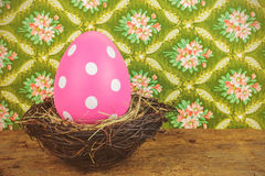 Pink dyed big easter egg in a bird nest on a wooden table stock photos