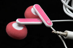 Pink Earbuds Closeup, macro, on black Royalty Free Stock Image