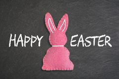 Pink Easter bunny with text `happy Easter`on a chalkboard background royalty free stock photo