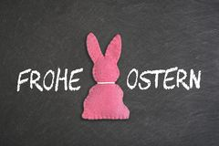 Pink Easter bunny with text `Frohe Ostern` on a chalkboard background.  Translation: `Happy Easter`. stock images