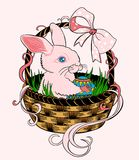 Pink Easter bunny sitting in a wicker basket. And holding a colorful egg Stock Photo