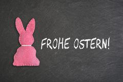 Pink Easter bunny with text `Frohe Ostern` on a chalkboard background. Transla stock images