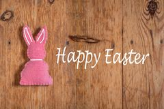 Pink Easter bunny with text `happy Eastern` on a wooden background stock images