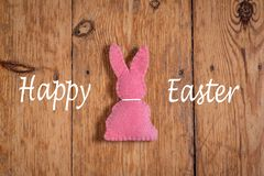 Pink Easter bunny with text `happy Eastern` on a wooden background stock photo
