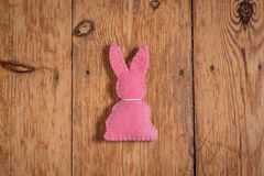 Pink Easter bunny with white collard on a wooden background. stock photos