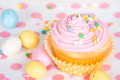Pink Easter cupcake with candy and sprinkles. Shallow depth of field Royalty Free Stock Images