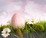 Pink easter egg with flowers in tall grass Stock Photography