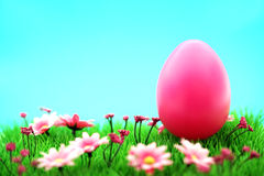 Pink easter egg on meadow with flowers & cyan background Royalty Free Stock Images