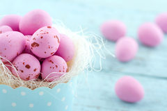Pink easter eggs in a blue cupcake cup. Pink easter eggs in a cupcake cup on light blue vintage wooden background Royalty Free Stock Images
