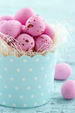 Pink easter eggs in a cupcake cup. On light blue vintage wooden background Stock Images